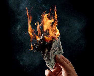 Man holding burning money